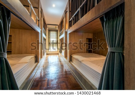 Hostel dormitory beds arranged in dorm room with white plain bunk bed in dormitory.Hotel dormitory have many beds arranged in one room. Clean hostel small room with wooden bunk beds.