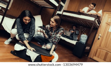 Hostel for Young People. Best Friends Traveling. Small Room in Hostel. spend time Together. bunk beds in room. Smiling People.. sit on bed. girl helps. tried to close valise. laugh at girls