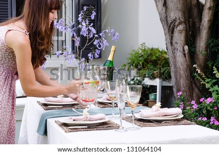 Hostess bringing water jug to the table set for a garden party