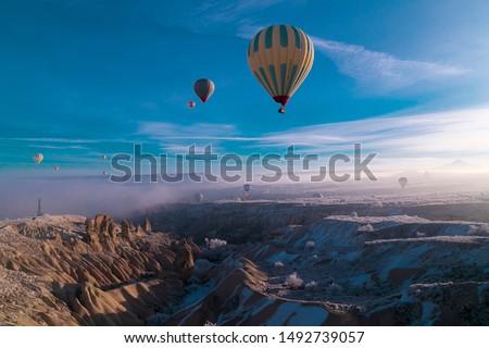Hot air ballons flying over Cappadocia National Park Göreme Turkey, fogyy air