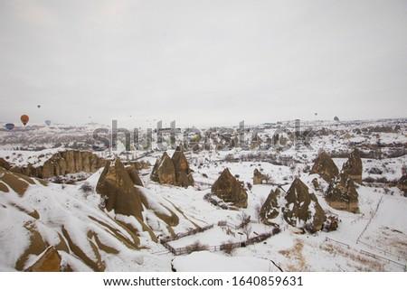 Hot air ballons flying over flying over spectacular Cappadocia National Park Göreme Turkey, foggy and snowy air