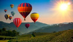 Hot air balloon above high mountain at sunrise or sunset.