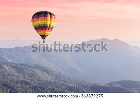 Hot air balloon above high mountain at sunset