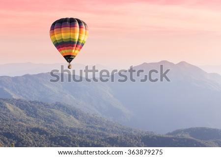 Stock Photo Hot air balloon above high mountain at sunset