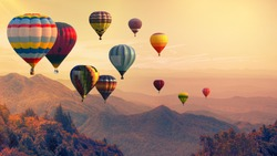 Hot air balloon above high mountain at sunset, filtered background