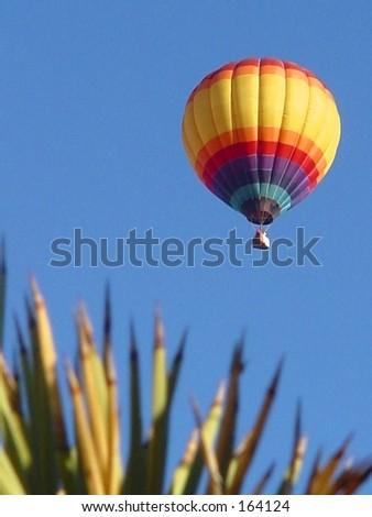 Hot air balloon against blue sky in desert
