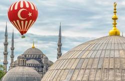Hot air balloon flying cupola dome semi-dome and apse Hagia Sophia or Aya Sofya in Istanbul Turkey