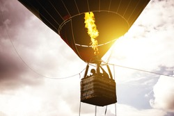 Hot air balloon flying in a cloudy sky at sunrise - Image of balloon silhouette flight over the sky