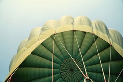 Hot air balloon flying in the blue sky in Green colour fabric parachute open and the ropes hook with the basket