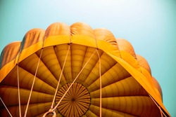 Hot air balloon flying in the blue sky with orange colour fabric parachute open and the ropes hook with the basket