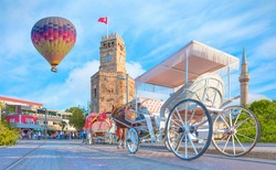 Hot air balloon flying over Antalya clock tower at Republic Square, traditional phaeton is waiting for customers in the foreground - Antalya, Turkey