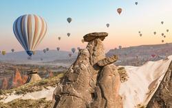 Hot air balloon flying over fairy chimneys and rock landscape at Cappadocia Turkey