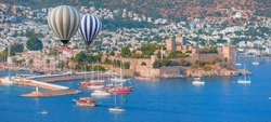 Hot air balloon flying over Saint Peter Castle (Bodrum castle) and marina in Bodrum, Turkey