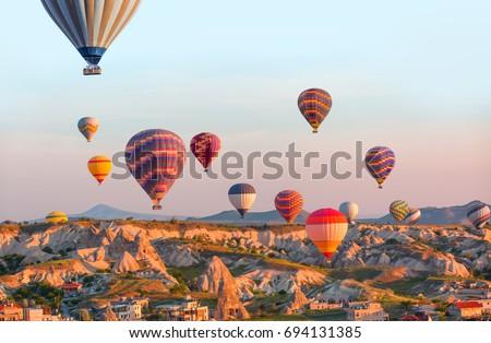 Hot air balloon flying over spectacular Cappadocia - Shutterstock ID 694131385