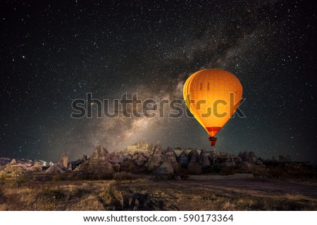 Hot air balloon flying over spectacular Cappadocia under the sky with milky way and shininng star at night (with grain)