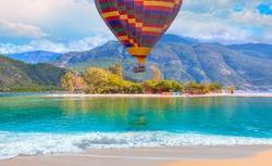 Hot air balloon flying over spectacular oludeniz lagoon with rainbow - Fethiye, Turkey