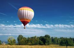hot air balloon in blue cloudy sky