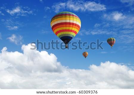 Hot air balloon in the cloudy blue sky