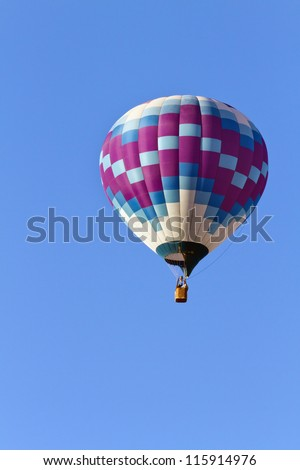 Hot air balloon moving up in blue sky