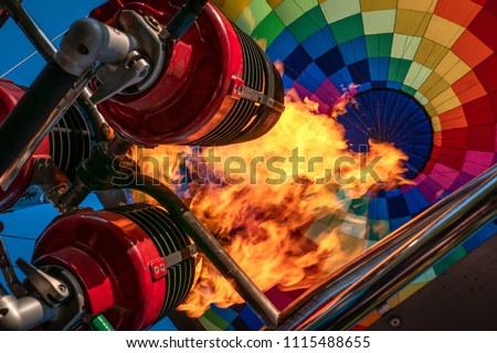 Hot air balloon or aerostat, bright burning fire flame from gas burner equipment, close up from inside