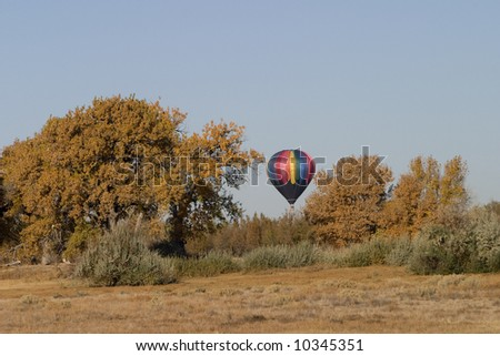 hot air balloon over horizon preparing to land in dry south eastern Colorado (Arkansas River Valley) in a late autumn, clear sky, copy space