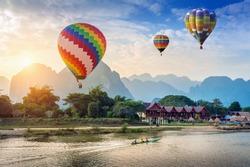 Hot air balloon over Nam Song river at sunset in Vang vieng, Laos.
