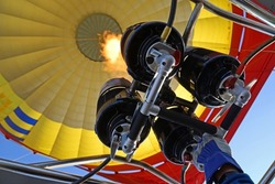 Hot air balloon pilot has his hand on the gas burner and filling in hot air into a yellow balloon