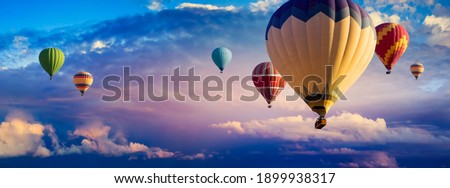 Hot Air Balloon Ride at sunrise background for wide banner of travel agency or adventure tour. Morning hot-air balloon flight with beautiful clouds. Romance of ballooning in a good weather.