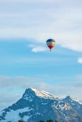 Hot air balloon rises over the Alps mountains