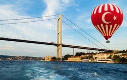 Hot air balloon Turkish flag flying over Istanbul bridge Bosporus. Fatih Sultan Mehmet Bridge Turkey. Travel concept.