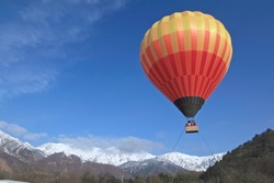 Hot air balloon with vivid colors - blue sky and snow background.