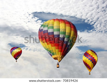 Hot Air Balloons Ascending Through Holes in the Clouds
