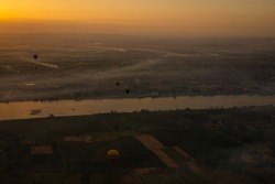 Hot air balloons at sunrise above Luxor, Egypt. The city is covered in thick morning fog.