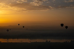 Hot air balloons at sunrise in Luxor, Egypt. The city is covered in thick morning fog.