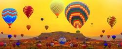 Hot air balloons. Balloons tour above high mountain at sunset. Cappadocia at sunrise Adventures on Turkey.