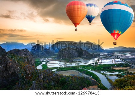 Hot air balloons floating up to the sky over mountain
