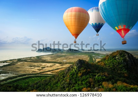 Hot air balloons floating up to the sky over mountain at the sea - Shutterstock ID 126978410