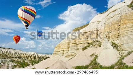 Hot air balloons flying over Love valley at Cappadocia, Anatolia, Turkey. Volcanic mountains in Goreme national park.