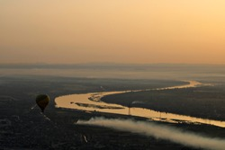 Hot air balloons flying over the Nile River in Luxor, Egypt at sunrise.