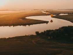 Hot Air Balloons in Ryazan, Russia 18 july 2021. Colorful hot air balloon epic flying over the fog at sunrise with beautiful sky background. High altitude aerial drone wide view