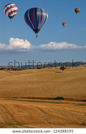 Hot-air Balloons over Countryside in Typical Summer Tuscan Landscape