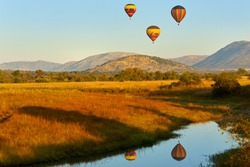 Hot air balloons with tourists above the Pilanesberg reserve. Three hot air balloons, decorated safari motifs against blue sky, mountains on background. Holiday Safari in South Africa.