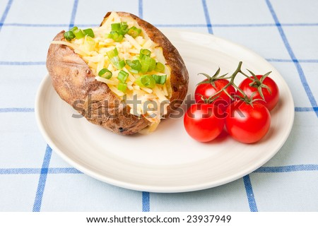 Hot and crispy baked potato stuffed with cheddar cheese, coleslaw and tomatoes