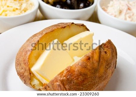 Hot and crispy baked potato stuffed with melting butter