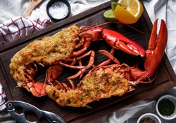 Hot and freshly baked halved Lobster with butter. Fresh, juicy, tasty and flavorful bright red Maine Lobster or American lobster on a hand of waitperson, ready to be served.