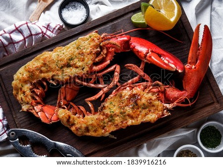 Hot and freshly baked halved Lobster with butter. Fresh, juicy, tasty and flavorful bright red Maine Lobster or American lobster on a hand of waitperson, ready to be served. Stockfoto ©