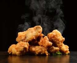 Hot and spicy bbq chicken wings with with green salad leaf and steam smoke on black background