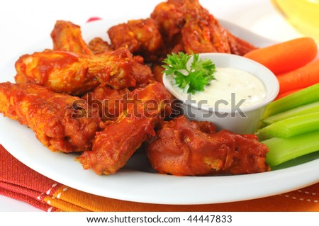 Hot and spicy buffalo chicken wings with fresh vegetables.