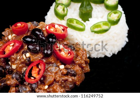 Hot and spicy Chili con Carne garnished with red peppers and rice with green pepper.  On black - stock photo