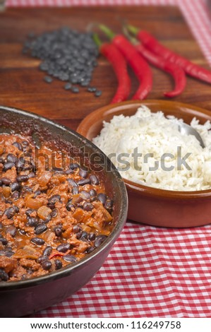 Hot and spicy Chili con Carne in the frying pan with rice. Whole red peppers and raw black beans in the background.